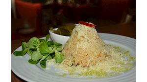 Risotto s kuřecím masem a zeleninou sypané sýrem, kyselý okurek